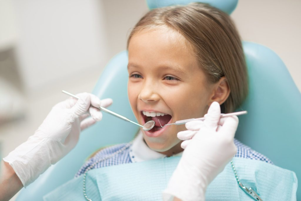 A young girl sits in a dental exam chair receiving a dental checkup
