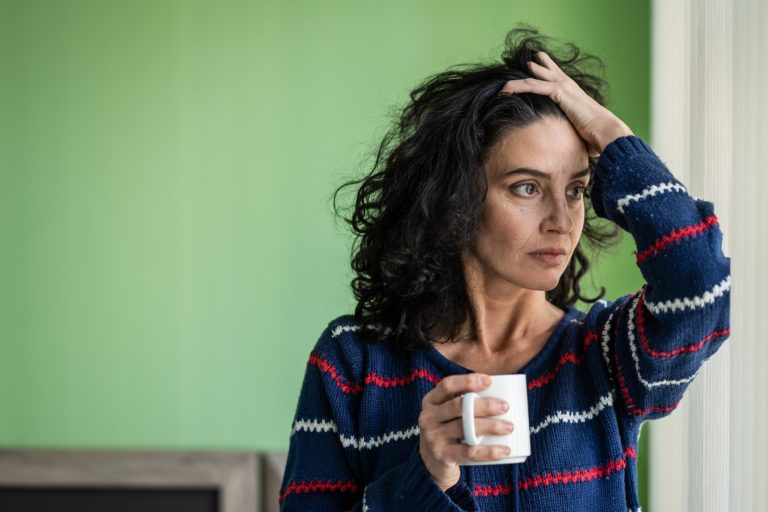 A stressed looking woman holding a coffee mug