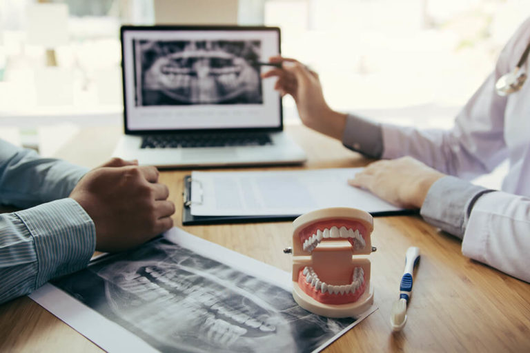 A dentist reviews dental x-rays with a patient while seated across a desk from each other