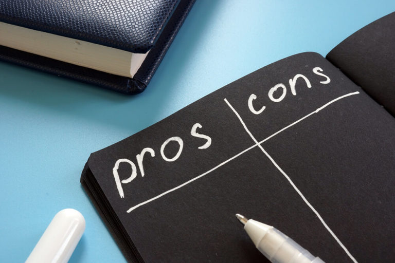 An open notebook with a pros and cons chart written on the open page